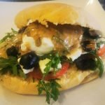 perfect mediterranean sandwich with arugula and poached egg